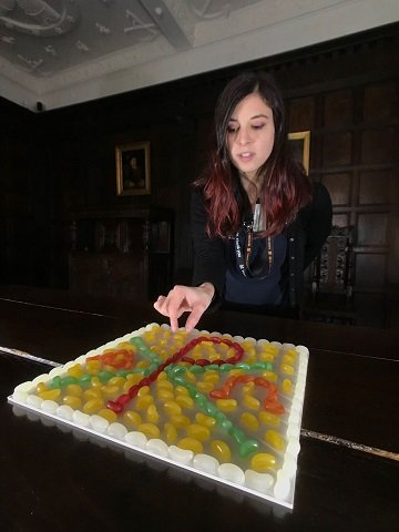 conservation assistant mary girerd with jelly bean chi-ro symbol which features on the stained glass panel